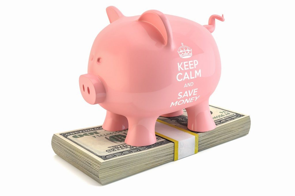 """pink piggy bank with the words """"keep calm and save money"""" on it standing on top of stack of hundred dollar bills."""