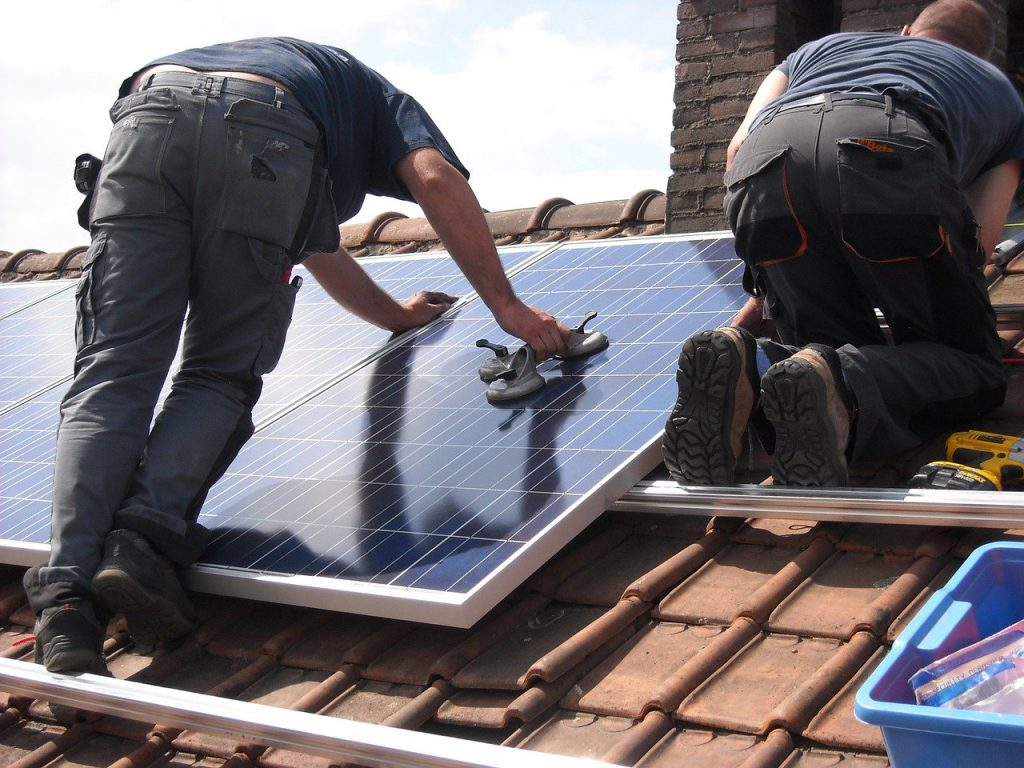 man standing on a roof leaning on a solar panel.