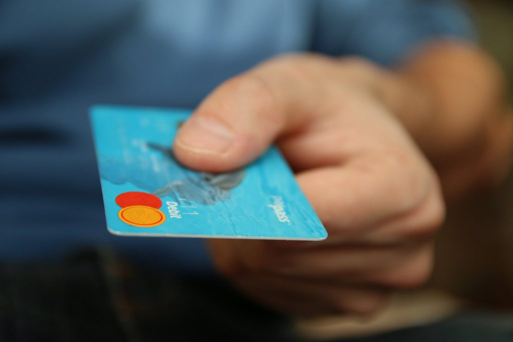 mans hand holding a blue credit card