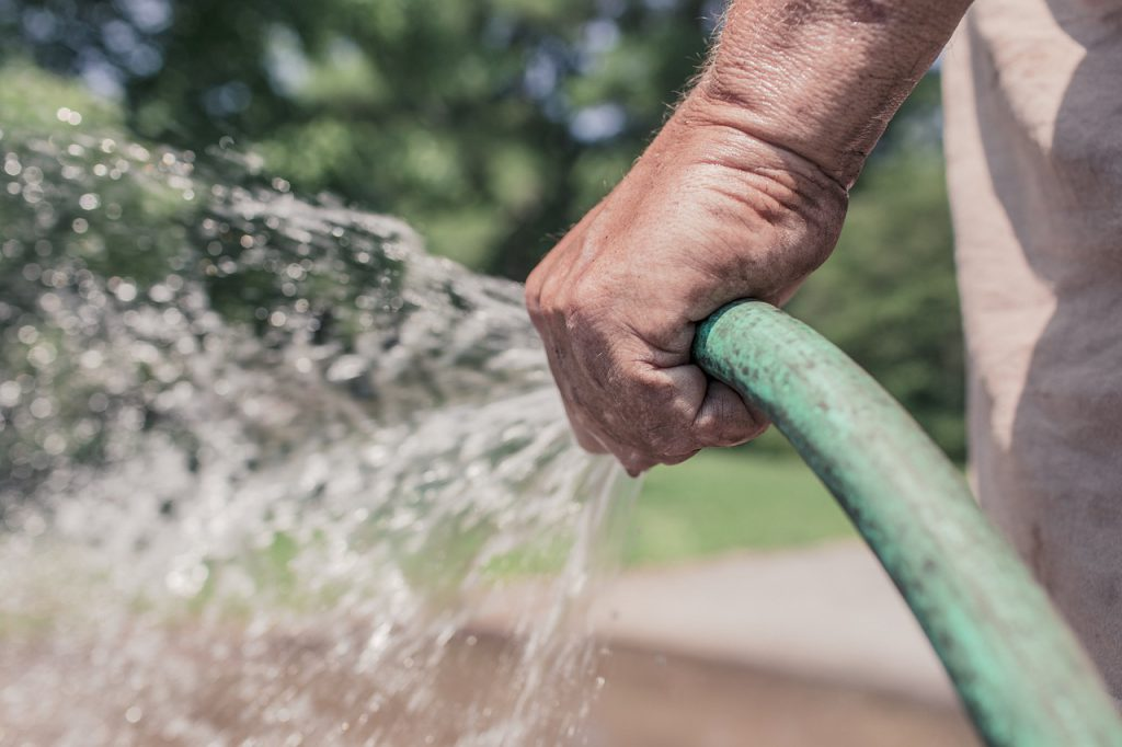 mans hand holding a green hose with water coming out of it