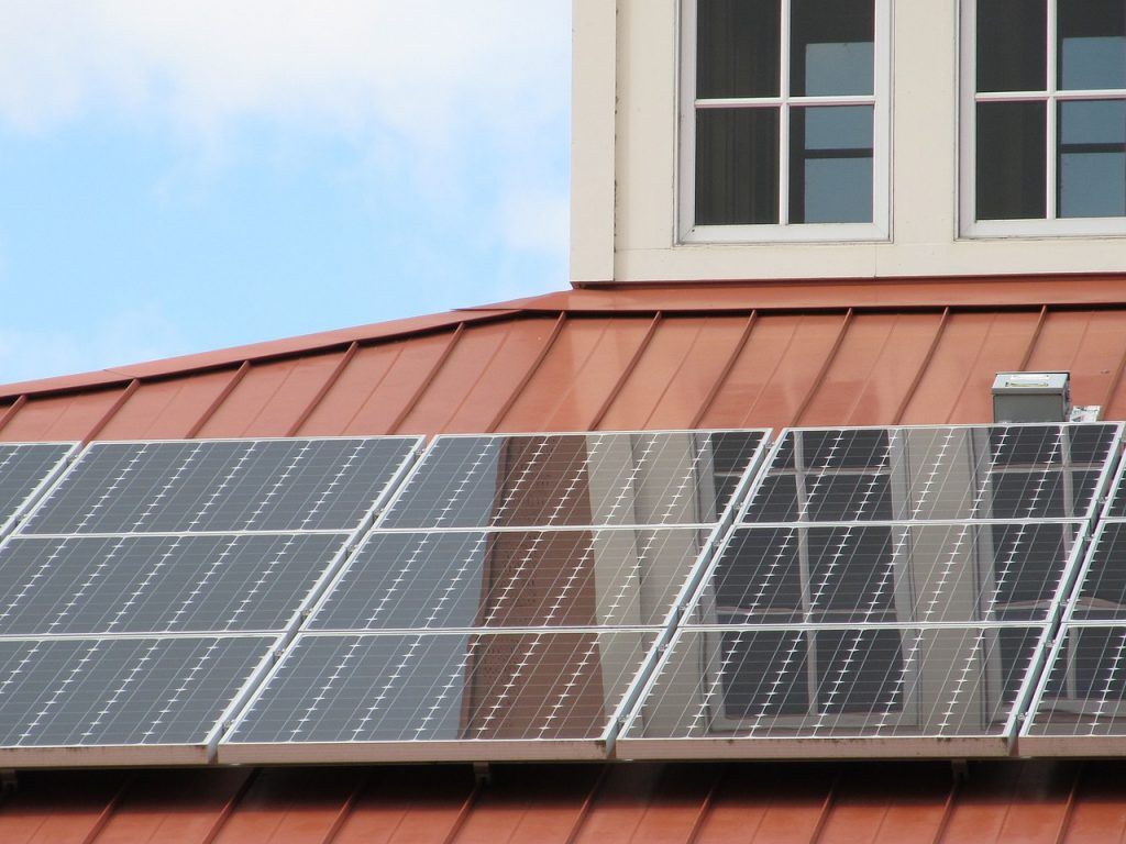 clean solar panels on a red tin roof