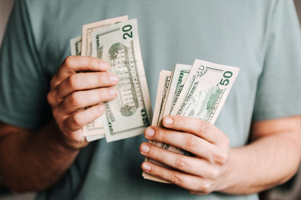 caucasian hands counting large money bills.