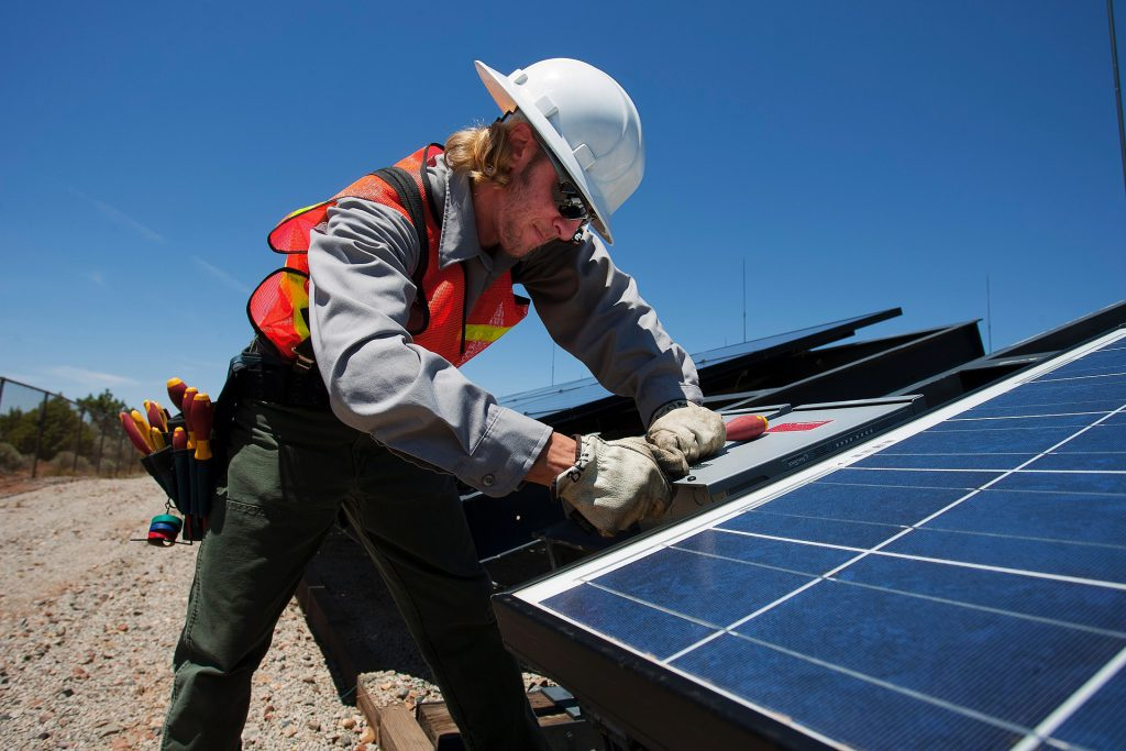 caucasian man with a utility belt working on a solar panel
