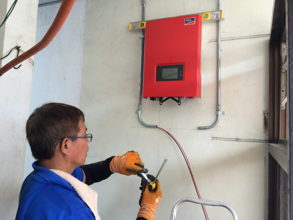 red solar inverter on a wall with a man looking at the wires.