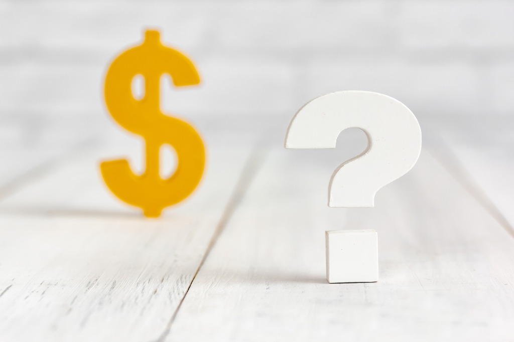 yellow money sign next to a white question mark
