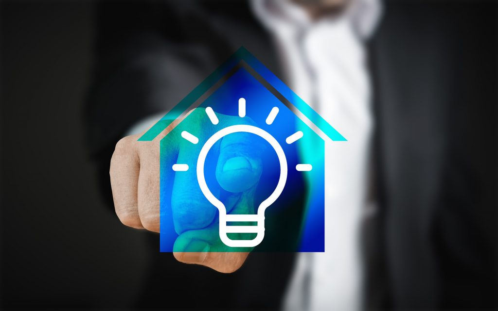 person in a suit pressing on a blue house with a light bulb in the middle of it