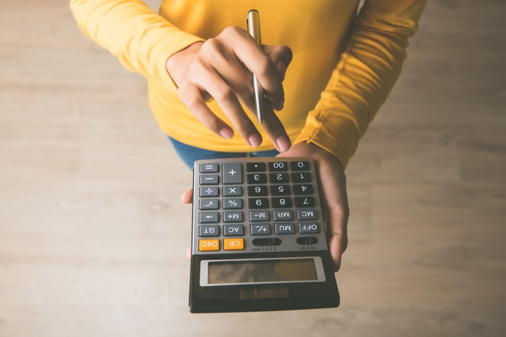 person with a mustard yellow sweater holding a calculator in one hand and a pencil in the other.