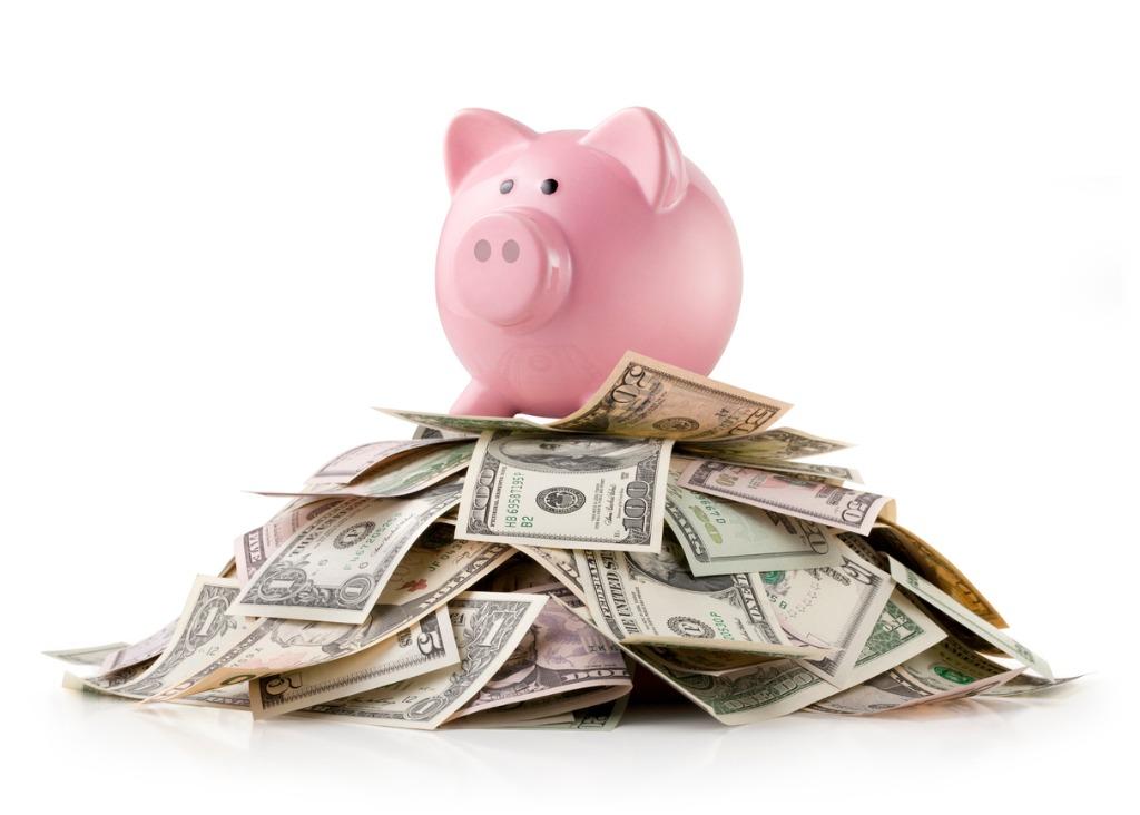 a pink piggy bank sitting on top of hundreds of dollar bills.