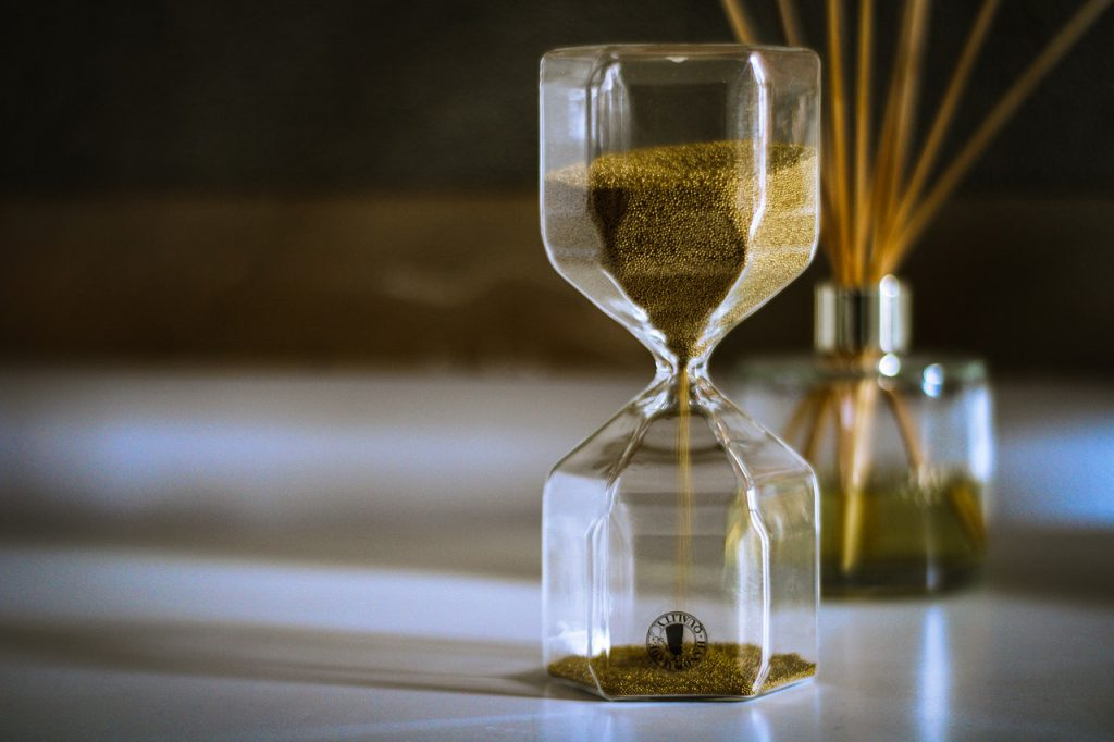 hourglass with brown sand dropping from the top to bottom