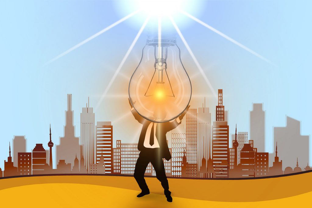 man in a suit holding up a light bulb to the sun