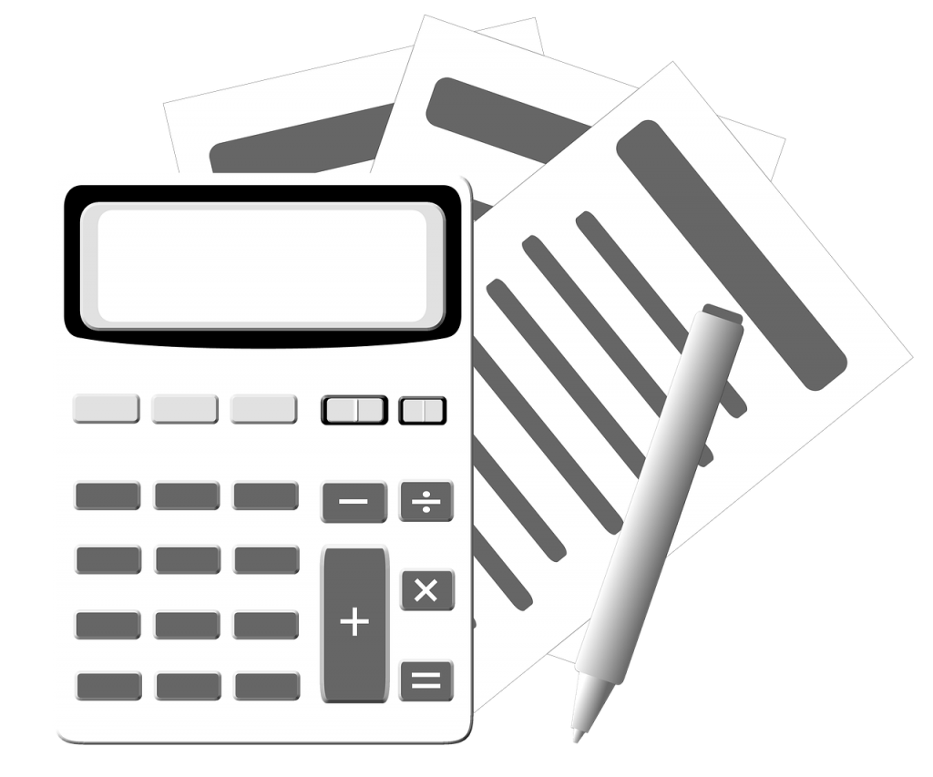 calculator in front of papers and a pen