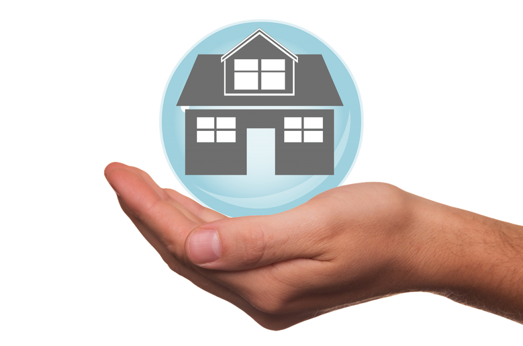 person's hand with a house hovering over it in a bubble