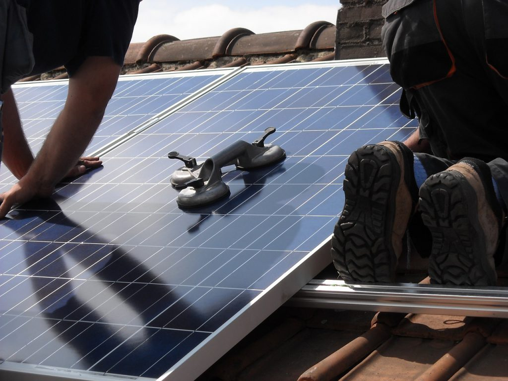 solar panels being installed by two men on a roof