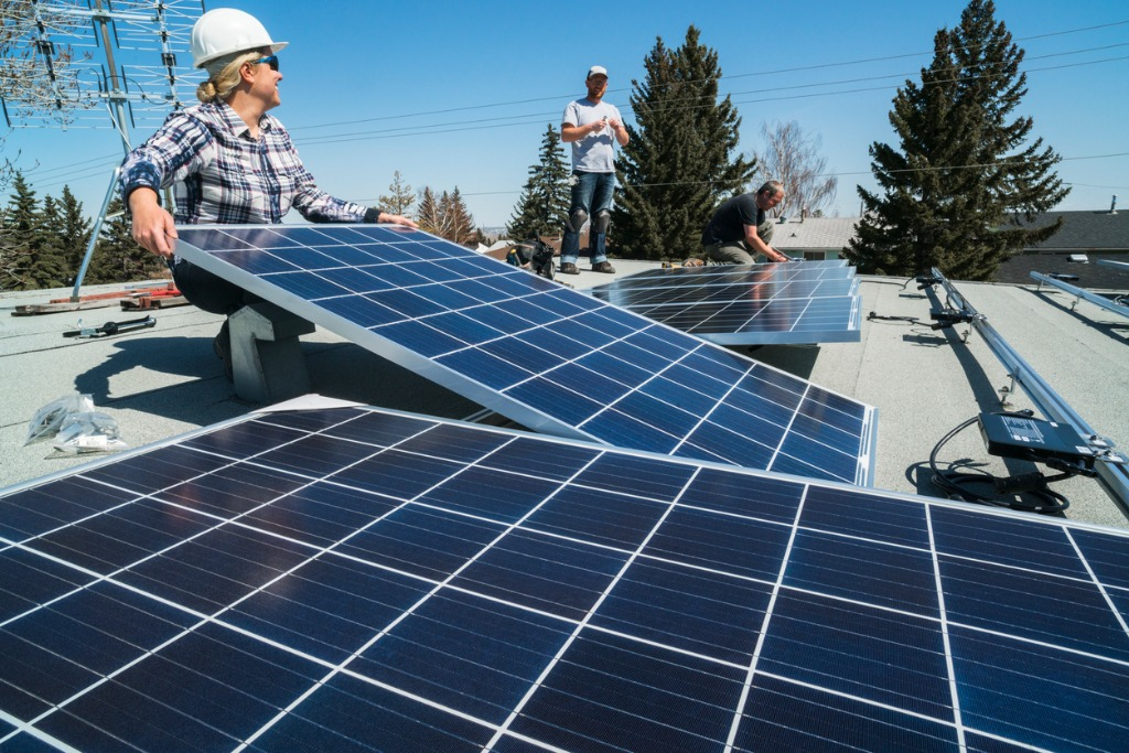people on a roof installing solar panels