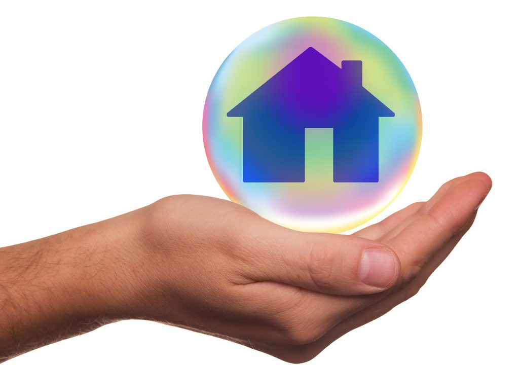 person's hand with a house in a bubble over the palm